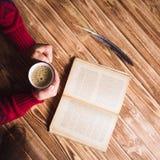 Mujer joven en un suéter rojo que sostiene una taza de café y que lee un libro Fotos de archivo libres de regalías