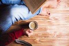 Mujer joven en un suéter rojo que sostiene una taza de café y que lee un libro Imagenes de archivo