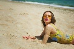 Mujer joven en un traje de baño cerrado que miente en la arena imagen de archivo libre de regalías