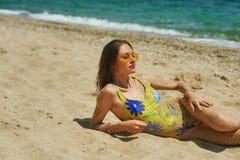 Mujer joven en un traje de baño cerrado que miente en la arena fotos de archivo