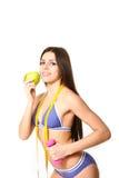 Mujer joven en un traje de baño con la manzana, la cinta métrica y el dumbbel Foto de archivo libre de regalías