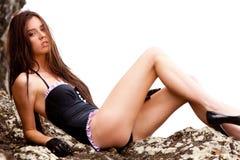 Mujer joven en un traje de baño que descansa en rocas Foto de archivo
