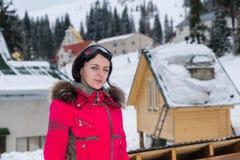 Mujer joven en un traje de esquí rojo y con las gafas del esquí que colocan nieve Foto de archivo