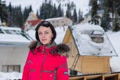 Mujer joven en un traje de esquí y con las gafas del esquí que colocan nieve-cov Imagenes de archivo