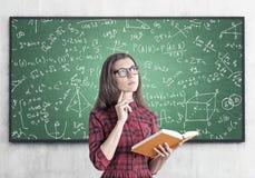Mujer joven en un vestido con un libro, fórmulas Imagen de archivo libre de regalías