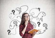 Mujer joven en un vestido con un libro, preguntas, flechas Imagen de archivo libre de regalías