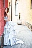 Mujer joven en un vestido que se inclina contra la pared Imagen de archivo