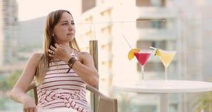 Mujer joven en un vestido que se sienta en el balcón en el hotel almacen de metraje de vídeo