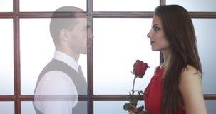 Mujer joven en un vestido rojo con las flores en sus manos almacen de video