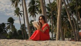 Mujer joven en un vestido rojo que camina por el mar Ella está utilizando una tableta y una sonrisa metrajes