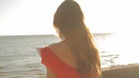 Mujer joven en un vestido rojo que camina en una playa soleada Ella está utilizando una tableta y una sonrisa almacen de video