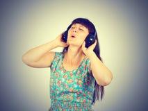 Mujer joven en un vestido verde que escucha la música con los auriculares Imágenes de archivo libres de regalías