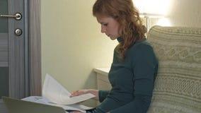 Mujer joven en un vestido verde que se sienta en el sofá con un ordenador portátil, funcionamiento, estudiando documentos, té de  metrajes