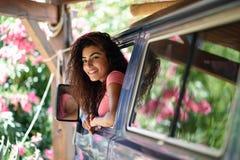 Mujer joven en una autocaravana en acampar hermoso con las flores rosadas foto de archivo libre de regalías
