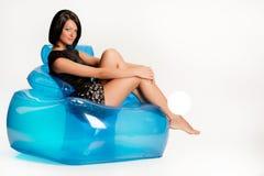 Mujer joven en una butaca inflable azul imágenes de archivo libres de regalías