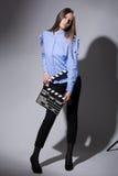 Mujer joven en una camisa rayada con una chapaleta de la película Imagen de archivo