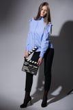 Mujer joven en una camisa rayada con una chapaleta de la película Fotografía de archivo