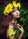 Mujer joven en una guirnalda amarilla en hojas Imagenes de archivo