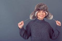 Mujer joven en una imagen gris del estudio del suéter aislada en el sombrero de piel del fondo que lleva gris fotos de archivo