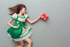 Mujer joven en una opinión superior del vestido de St Patrick del día festivo del ` s que sostiene la caja de regalo Imagenes de archivo