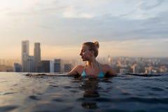 Mujer joven en una piscina del top del tejado con la opinión hermosa de la ciudad Fotografía de archivo libre de regalías