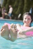 Mujer joven en una piscina que se sostiene sobre una balsa inflable con los pies que se pegan fuera del agua Imagenes de archivo
