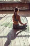 Mujer joven en una posición de loto dentro Imagen de archivo libre de regalías