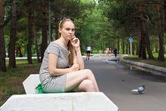 Mujer joven en una sentada rayada del vestido Fotografía de archivo libre de regalías