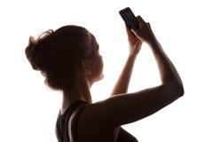 Mujer joven en una sombra de una silueta con el teléfono Fotografía de archivo