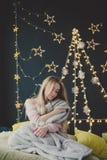 Mujer joven en una tela escocesa que presenta contra la perspectiva de las guirnaldas de la Navidad fotografía de archivo libre de regalías