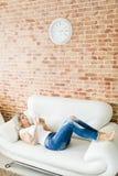 Mujer joven en vaqueros usando el teléfono elegante que miente comfortablemente en el sofá blanco fotos de archivo