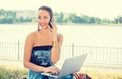 Mujer joven en vestido azul que habla en el teléfono móvil al aire libre foto de archivo libre de regalías