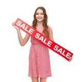 Mujer joven en vestido con la muestra de la venta Imagen de archivo