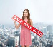Mujer joven en vestido con la muestra de la venta Foto de archivo libre de regalías