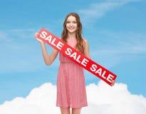 Mujer joven en vestido con la muestra de la venta Imágenes de archivo libres de regalías