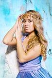 Mujer joven en vestido de la princesa en un fondo de una hada del invierno Foto de archivo