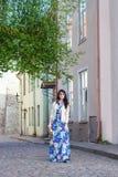 Mujer joven en vestido largo que camina en la ciudad vieja de Tallinn Imagen de archivo