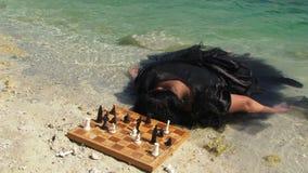Mujer joven en vestido negro con el tablero de ajedrez almacen de video