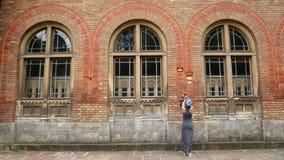 Mujer joven en vestido negro que camina en la acera, en el fondo Wall Street bricked viejo, posibilidad muy remota de detrás metrajes