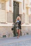 Mujer joven en vestido negro que camina en la calle de la ciudad foto de archivo