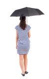 Mujer joven en vestido que camina debajo de un paraguas Imagen de archivo
