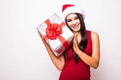 Mujer joven en vestido rojo con el regalo de la Navidad del control del sombrero de santa Fotografía de archivo libre de regalías