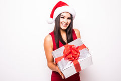 Mujer joven en vestido rojo con el regalo de la Navidad del control del sombrero de santa Imagen de archivo