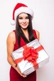 Mujer joven en vestido rojo con el regalo de la Navidad del control del sombrero de santa Foto de archivo libre de regalías