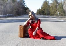 Mujer joven en vestido rojo en el camino con equipaje rojo Foto de archivo