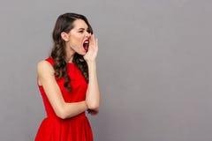 Mujer joven en vestido rojo que grita Fotografía de archivo libre de regalías