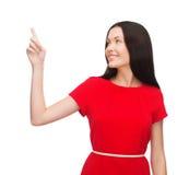 Mujer joven en vestido rojo que señala su finger Imágenes de archivo libres de regalías