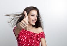 Mujer joven en vestido rojo que soporta los pulgares imagenes de archivo