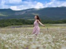 Mujer joven en vestido sin mangas rosado en el prado de la manzanilla Foto de archivo libre de regalías