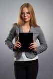 Mujer joven en vidrios con PC de la tableta en fondo gris Fotos de archivo